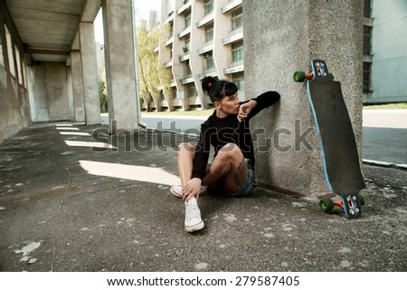 young fit woman with modern haircut sitting with longboard. she is in the shade of building. she wears jeans and sweatshirt. She has tattoos throughout her body. longboard has no prints or aerography - stock photo
