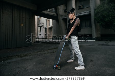 young fit woman with modern haircut standing with longboard. she is in the shade of building. she wears jeans and singlet. She has tattoos throughout her body. longboard has no prints or aerography - stock photo