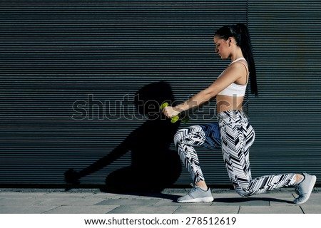 Young fit woman with strong body and perfect figure exercising with dumbbells outside on black wall background, athletic female toning with weights standing against copy space for your text message - stock photo