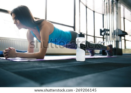 Young fit woman working out on yoga mat at gym - stock photo