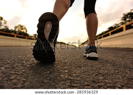 young fitness asian woman runner legs running on road - stock photo