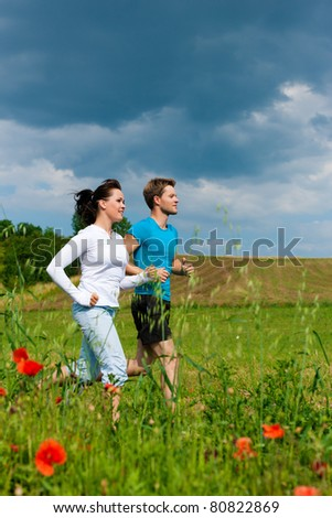 Young fitness couple doing sports outdoors; jogging on a green meadow in summer under a blue sky - stock photo