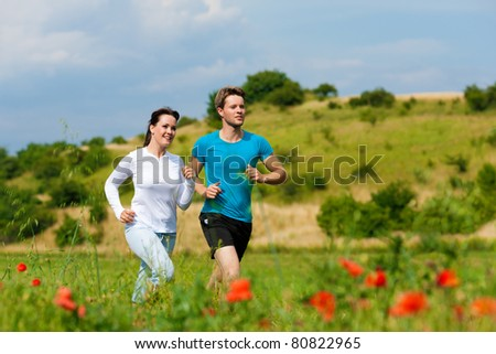Young fitness couple doing sports outdoors; jogging on a green meadow in summer under the sky with lots of clouds - stock photo