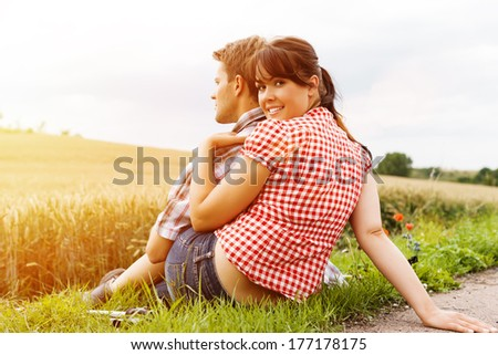 Young fitness couple doing sports outdoors, making a break from hiking in summer  - stock photo