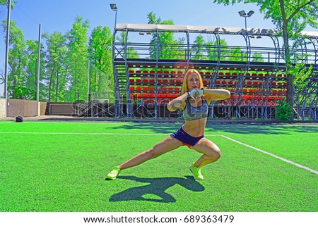 Young fitness girl doing different sport exercises on the artificial green soccer field