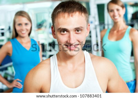 Young fitness instructor with gym people - stock photo