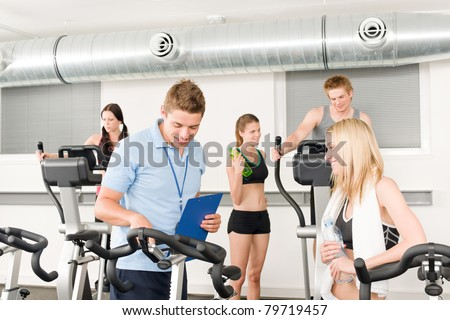 Young fitness instructor with gym people