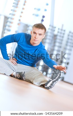 Young fitness man doing stretching exercises on the floor at the sport gym club