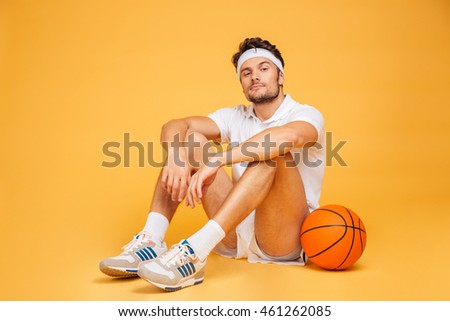 Young fitness man resting on the floor isolated on a orange background and looking at camera