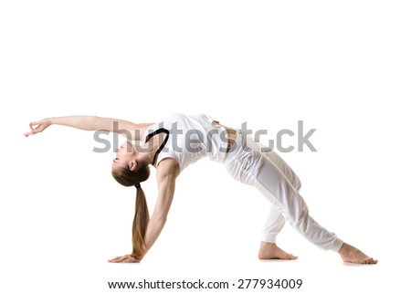 Young fitness model in white sportswear doing yoga or pilates training, exercise bridge, asana Camatkarasana, Wild Thing, Dancing Dog yoga pose, side view