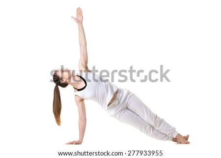 Young fitness model in white sportswear doing yoga or pilates training, Side Plank Pose, Vasisthasana, front view - stock photo