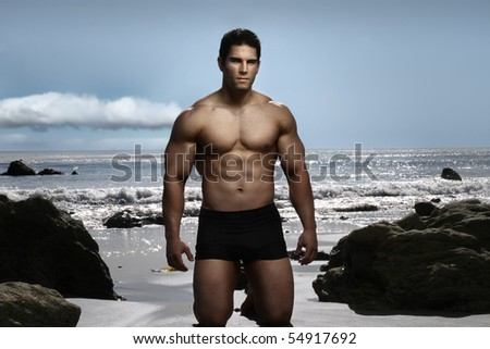 Young fitness model on the beach - stock photo