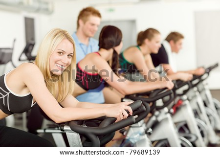 Young fitness people with instructor at gym - stock photo