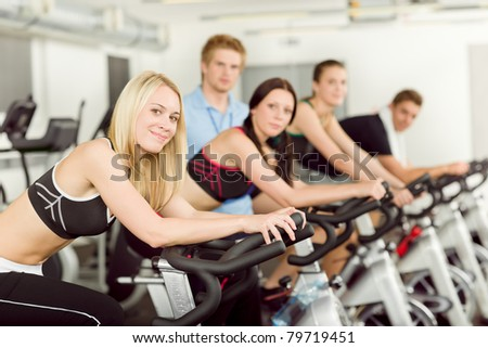 Young fitness people with instructor at gym