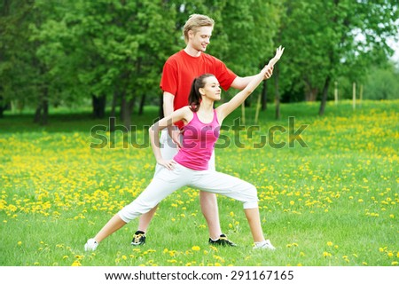 Young fitness woman and male instructor doing physical stretching exercises during outdoors sport training - stock photo