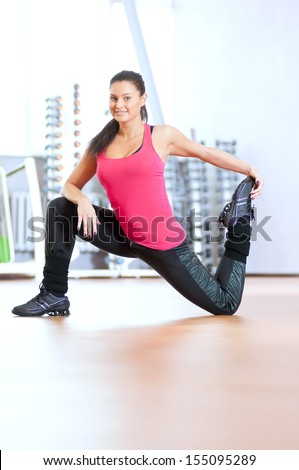 Young fitness woman doing stretching exercises on the floor at the sport gym club
