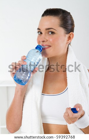 young fitness woman drinking water after workout - stock photo