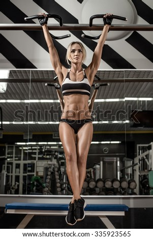 young fitness woman, execute exercise on horizontal bar in gym, vertical photo - stock photo