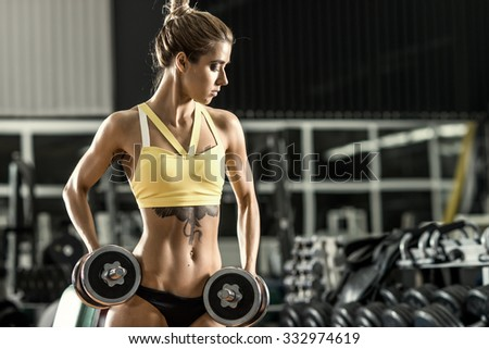 young fitness woman execute exercise with dumbbells in gym, horizontal photo - stock photo