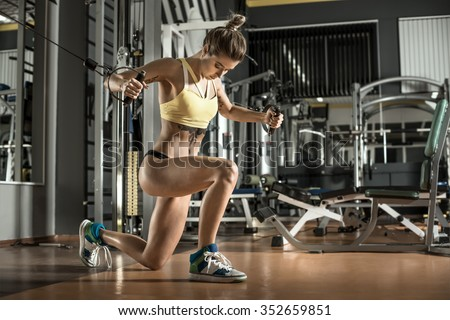 young fitness woman execute exercise with exercise-machine Cable Crossover in gym, horizontal photo - stock photo