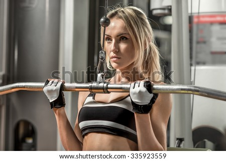 young fitness woman execute exercise with exercise-machine in gym, horizontal photo - stock photo