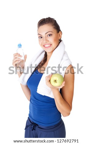 Young fitness woman holding bottle of water and apple isolated on white background