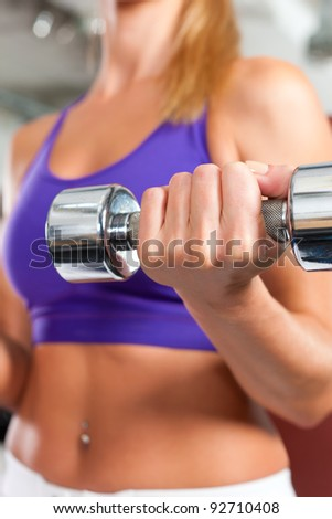 Young fitness woman is exercising with barbell in gym to strengthen the muscles - stock photo