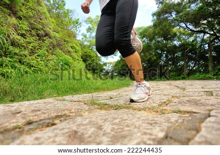 young fitness woman legs running at forest stone trail