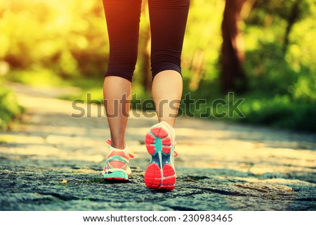 young fitness woman legs walking on forest trail  - stock photo