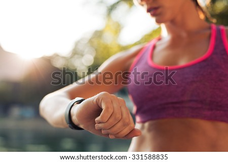 Young fitness woman looking at her smart watch while taking a break from sports training. Sportswoman checking pulse on fitness smart watch device. - stock photo