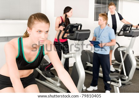 Young fitness woman on bicycle with gym instructor