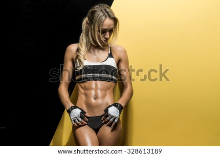 young fitness woman on black and yellow background, horizontal photo - stock photo