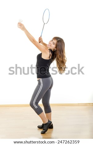 Young fitness woman playing badminton in sweat suit holding racquet and shuttlecock - stock photo
