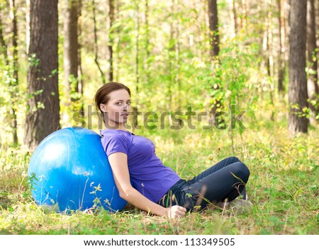 Young fitness woman relax after exercising with a fitness ball outdoors