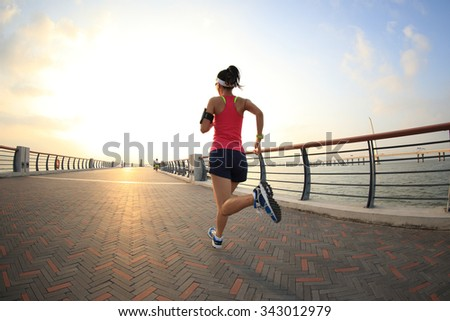 young fitness woman runner running at seaside - stock photo