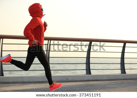 young fitness woman runner running at sunrise seaside - stock photo