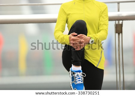 young fitness woman runner stretching legs at shanghai city - stock photo