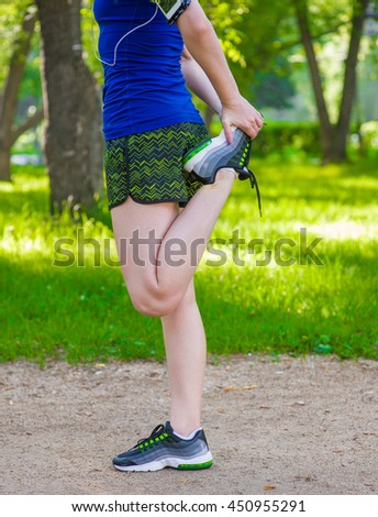 Young fitness woman runner stretching legs before run. Close up