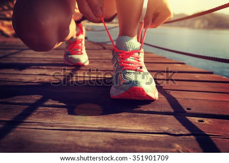 young fitness woman runner tying shoelace at seaside boardwalk - stock photo