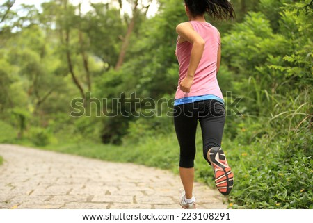 young fitness woman running at forest trail  - stock photo