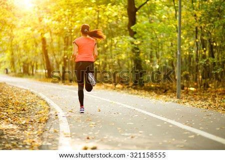 young fitness woman running at forest trail in park - stock photo
