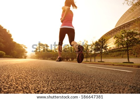 young fitness woman running at sunrise driveway  - stock photo