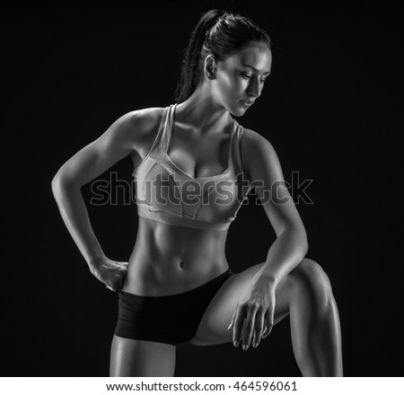Young fitness woman showing her perfect sculpted muscular and tight body