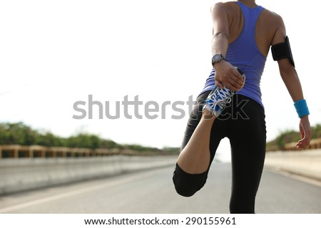 young fitness woman stretching legs before run - stock photo