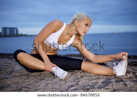 Young fitness woman stretching on a beach. - stock photo