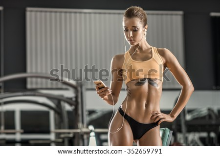 young fitness woman tired in gym and listen music with headset  - stock photo