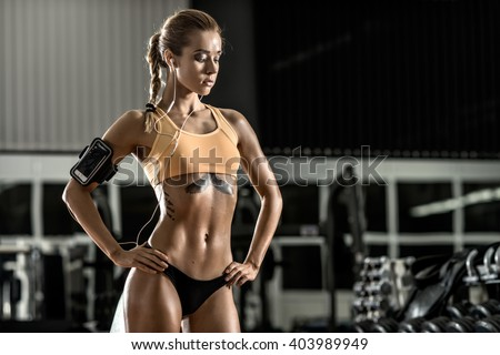 young fitness woman tired in gym and listen music with headset, horizontal photo - stock photo