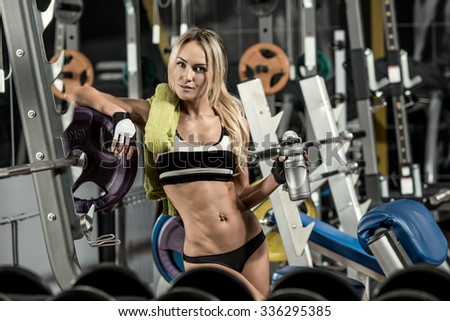 young fitness woman tired in gym hold shaker with sportive nutrition - protein of shaker , horizontal photo - stock photo