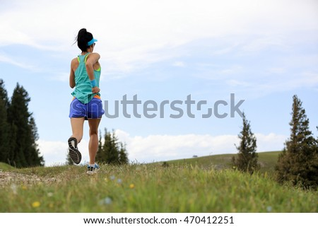 young fitness woman trail runner running on beautiful mountain peak