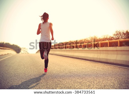 young fitness woman trail runner running  on city road - stock photo